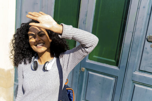 Laughing wiman shielding her eyes against the sun - FMOF00441