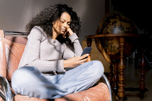 Woman sitting relaxed in armchair, using smartphone - FMOF00450
