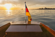 Germany, Baden-Wuerttemberg, Lake Constance, motorboat, German flag at sunset - SH02071