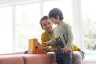 Father and son playing with a toy till - JOSF03084