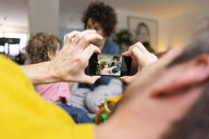 Mother and daughter playing in living room, fater taking smartphone pictures - JOSF03087