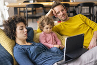 Family lying on couch watching movie on theit tablet - JOSF03108