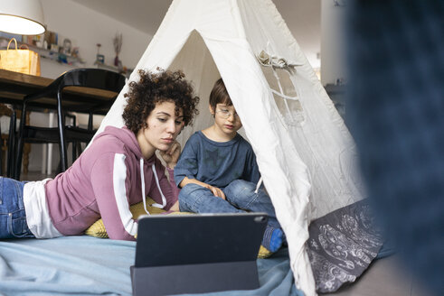 Mother and son lying in play tent, watching movie on tablet - JOSF03123