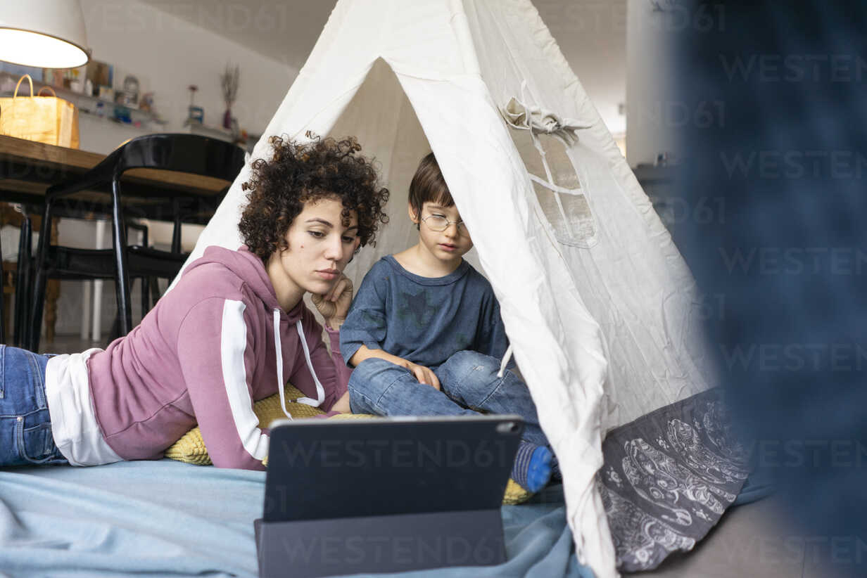 Mother and son lying in play tent, watching movie on tablet - JOSF03123 - Joseffson/Westend61