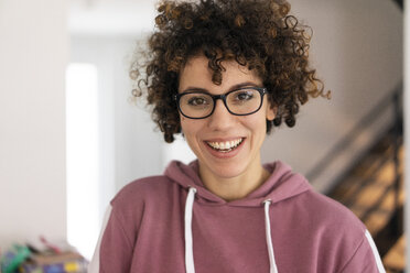 Portrait of a young woman with curly hair, wearing glasses - JOSF03129