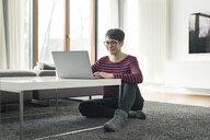 Portrait of woman sitting on the floor of living room using laptop - SBOF01822