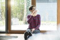 Woman sitting on the floor in front of terrace door drinking coffee - SBOF01825