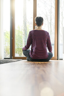Back view of woman sitting on the floor of living room meditating - SBOF01828