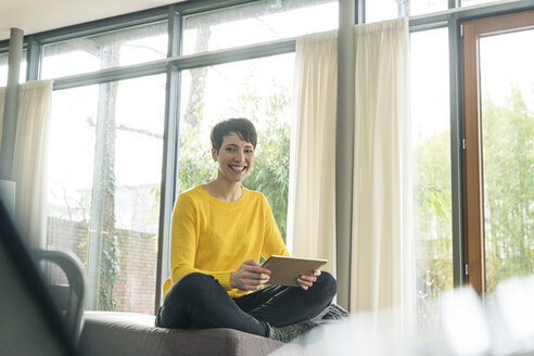 Portrait of happy woman with digital tablet sitting on couch in the living room - SBOF01834