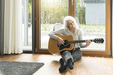 Mature woman sitting on the floor of living room playing guitar - SBOF01840