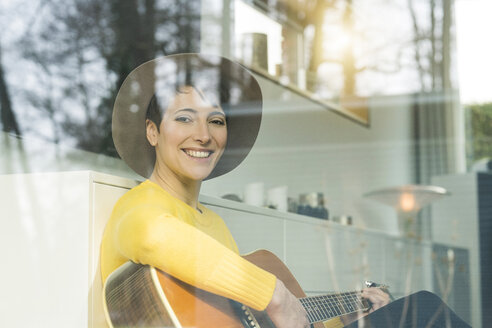 Portrait of smiling woman behind windowpane playing guitar - SBOF01843