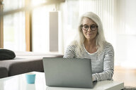 Portrait of mature woman using laptop at home - SBOF01846