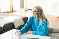 Portrait of smiling mature woman with cup of coffee at home - SBOF01849
