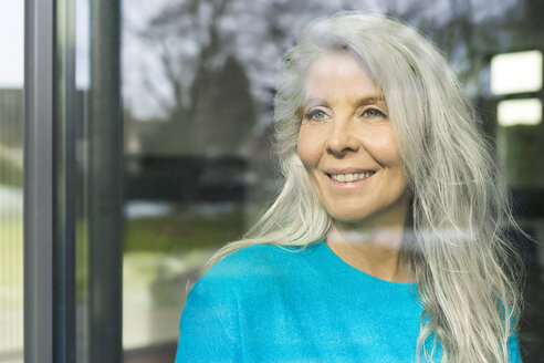 Portrait of happy mature woman looking out of window - SBOF01852