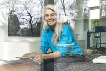 Portrait of smiling mature woman with digital tablet sitting on the couch at home looking out of window - SBOF01855