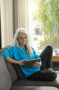 Portrait of mature woman sitting on the couch at home using digital tablet - SBOF01858