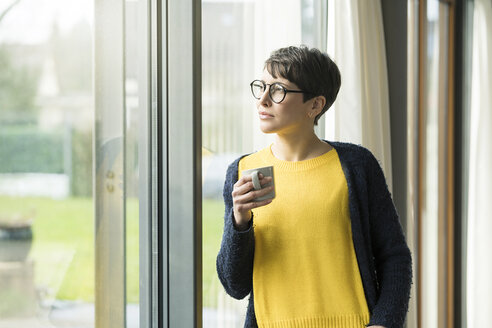 Portrait of woman with cup of coffee  looking out of window - SBOF01861