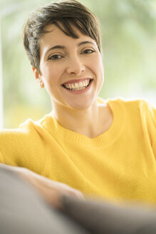 Portrait of happy woman with short brown hair wearing yellow pullover sitting on the couch at home - SBOF01873