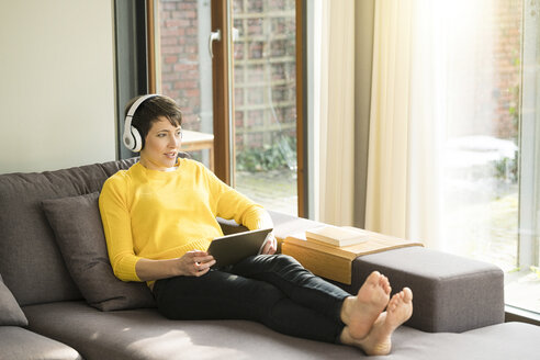 Portrait of woman with digital tablet sitting on the couch at home listening music with headphones - SBOF01876