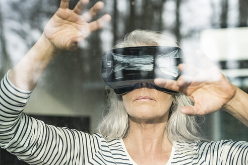 Portrait of mature woman behind windowpane using Virtual Reality Glasses - SBOF01882