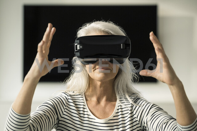 Portrait of mature woman using Virtual Reality Glasses at home - SBOF01885 - Steve Brookland/Westend61