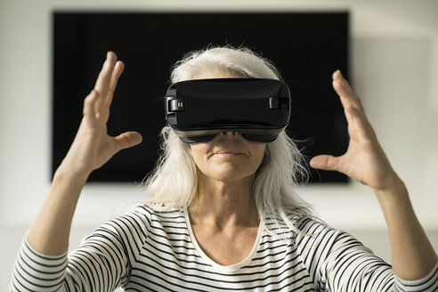 Portrait of mature woman using Virtual Reality Glasses at home - SBOF01885