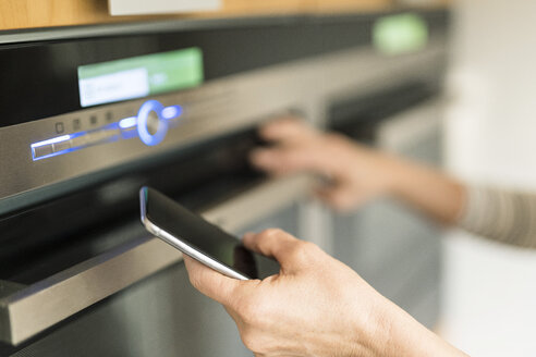 Hand of woman with smartphone checking oven in kitchen at her smart home - SBOF01888