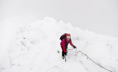 UK, Scotland, Glen Spean, woman climbing East ridge of Beinn a Caorainn in winter - ALRF01421