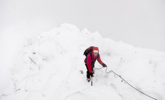UK, Scotland, Glen Spean, woman climbing East ridge of Beinn a Caorainn in winter - ALRF01421