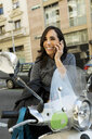 Happy woman with motor scooter talking on cell phone in the city - VABF02241