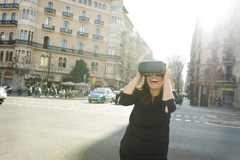 Excited woman wearing VR glasses in the city - VABF02250