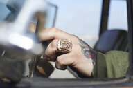 Man's hand with ring and tattoo at car steering wheel - AMEF00028