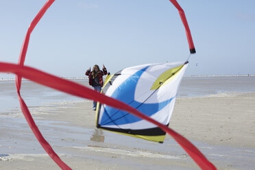 Germany, St Peter-Ording, girl flying kite on the beach - AMEF00034