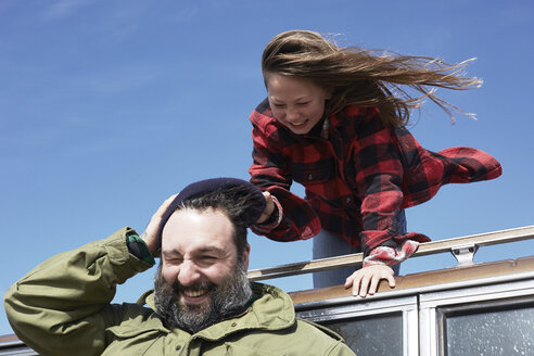 Playful daughter pulling cap from father's head - AMEF00037