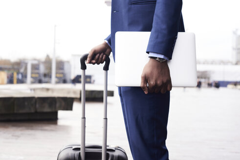 Crop of unrecognizable elegant businessman with laptop and baggage background in the street. London, UK. - IGGF00916