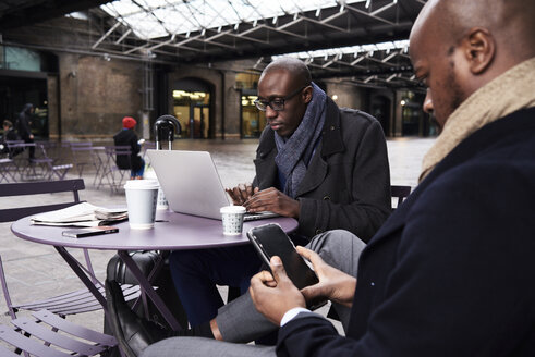 Two businessmen sitting at table of coffee shop using mobile devices - IGGF00922