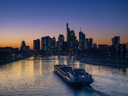 Germany, Hesse, Frankfurt, Skyline of financial district, Main river and Deutschherrn Bridge, cargo ship at sunset - AMF06803