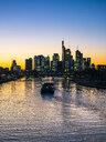 Germany, Hesse, Frankfurt, Skyline of financial district, Main river and Deutschherrn Bridge, cargo ship at sunset - AMF06812
