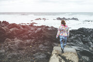 Portugal, Azores Islands, Sao Miguel, woman looking at the sea from rocky landscape - KIJF02412