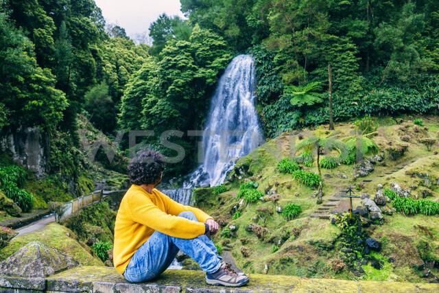 Portugal, Azores Islands, Sao Miguel, sitting man looking at a waterfall - KIJF02415 - Kiko Jimenez/Westend61