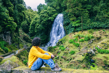 Portugal, Azores Islands, Sao Miguel, sitting man looking at a waterfall - KIJF02415