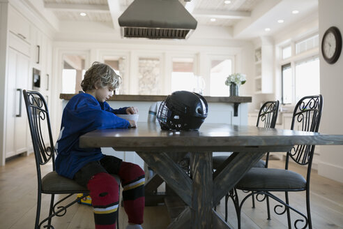 Boy in ice hockey uniform eating cereal table - HEROF26867