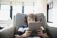 Boy with headphones using digital tablet in armchair - HEROF26930