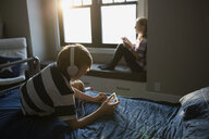 Brother and sister using digital tablets in bedroom - HEROF26933