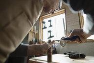 Carpenter using chisel on wood block in workshop - HEROF26972