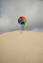 Woman with colorful umbrella standing on a dune - KBF00548