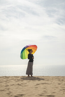 Woman with colorful umbrella standing at the beach - KBF00551