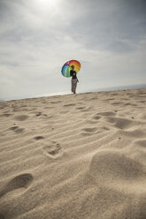 Woman with colorful umbrella standing at the beach - KBF00554