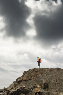 Woman with colorful umbrella standing on a hill at the beach - KBF00557