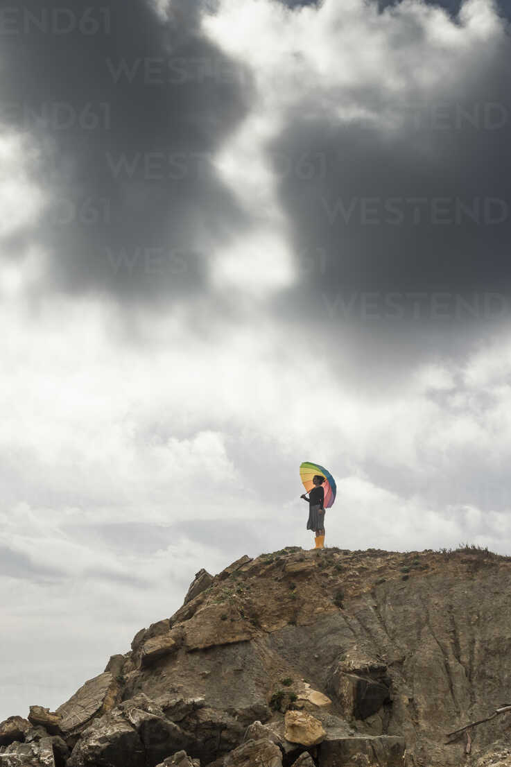 Woman with colorful umbrella standing on a hill at the beach - KBF00557 - Sebastian Kanzler/Westend61